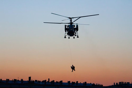 Helicopter silhouette with people hanging below.