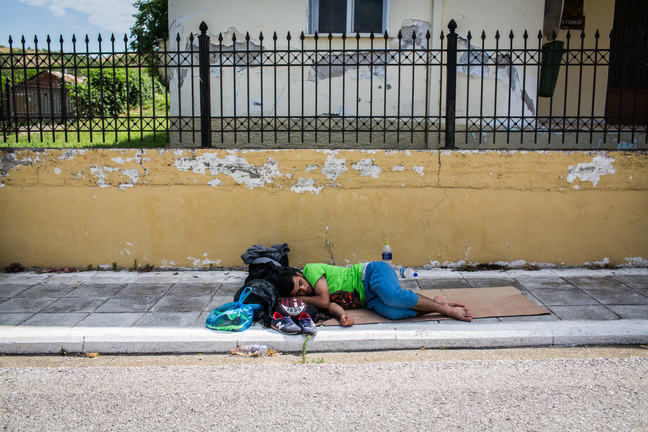Image of boy sleeping in street