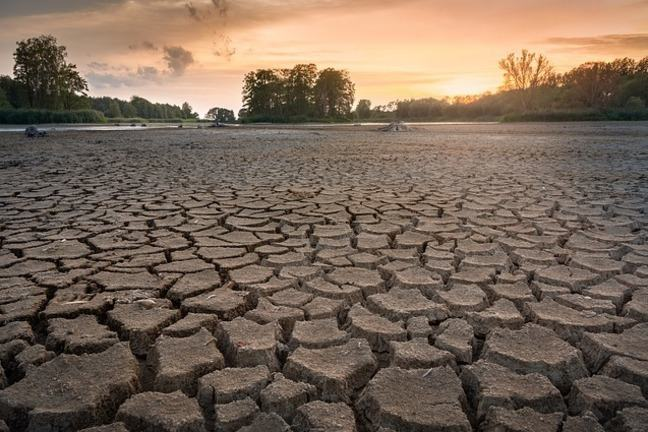 A landscape effected by drought with cracked dry muddy ground with a backdrop of forests and the sun setting.