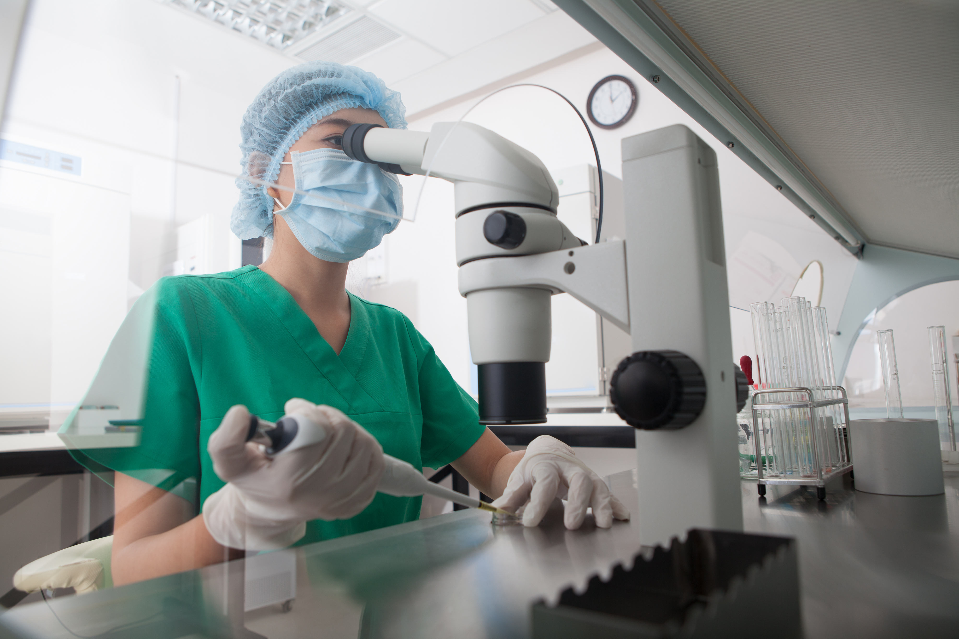 A woman looking through a microscope in a laboratory.