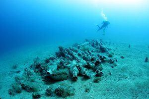 A diver exploring some amphora from a shipwreck