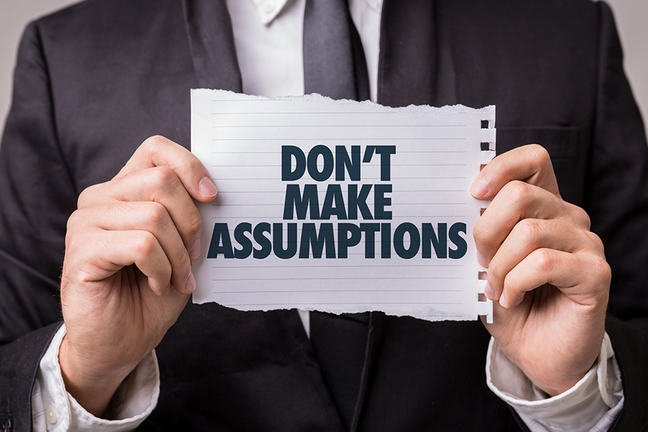 Business person holding a paper note saying 'Don't make assumptions'.