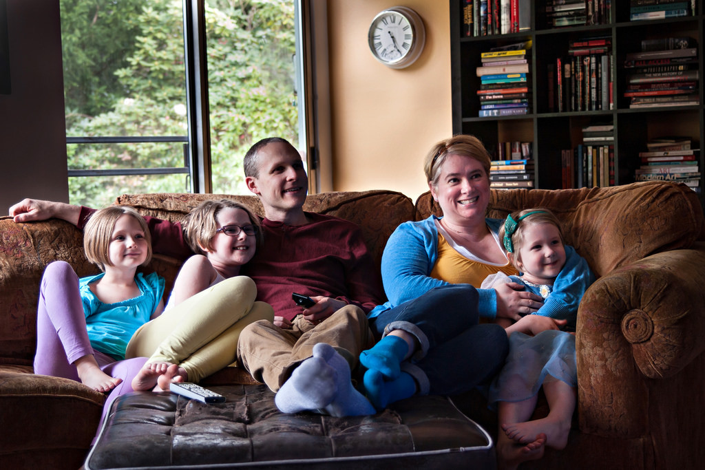 Family of 5 sitting on lounge smiling and watching television