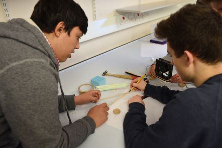 Two students draw and measure in an engineering lab.
