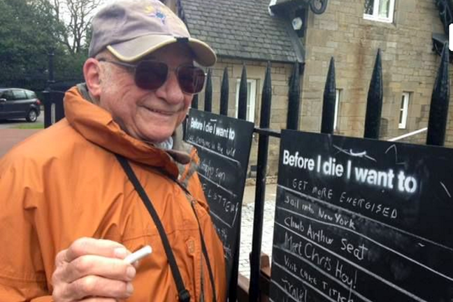 A man writes on a 'Before I die...' chalkboard outdoors