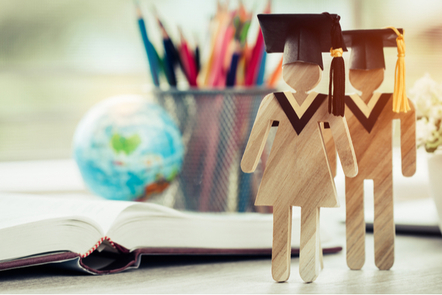Male and Female wooden figurines wearing mortar-board caps stand in front of an open textbook on a desk.