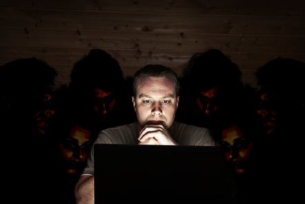 A man looks at his laptop screen, whilst others lurk behind him looking over his shoulder