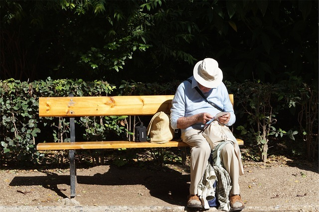 Elderly gentleman sitting on a bench reading a map