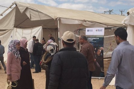 People standing outside a tent in a refugee camp next to a sign saying 'conference in a camp'