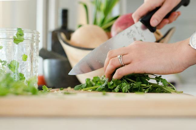 A close-up of a hand holding a kitchen knife and chopping herbs