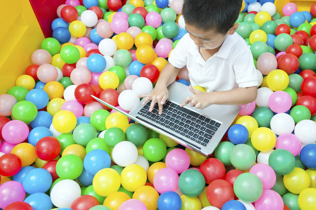a younger student on a laptop in a ball pool