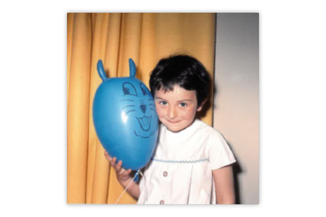 Photo of young girl holding a blue balloon