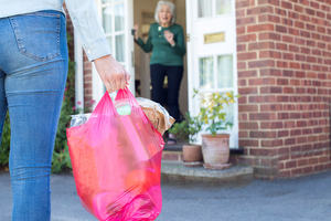 A woman arrives with a full bag of shopping at another woman's door