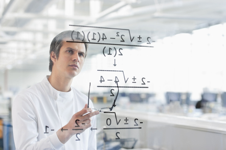 A man attempts to solve the mathematical equation written on a clear screen in front of him.