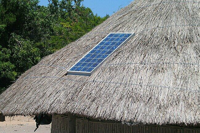 Photo of a solar panel on a straw roof hut