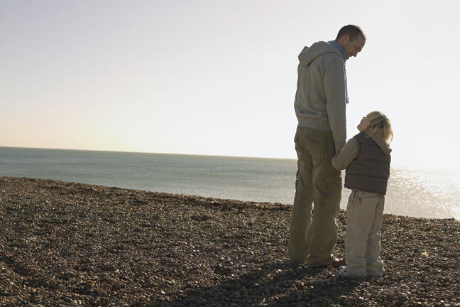 Man and small boy on a beach and holding hands