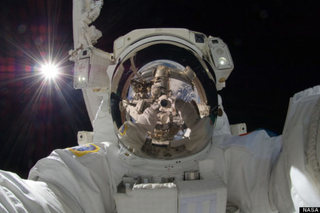 Space person floating in space in a space suit with the reflection of space in his or her helmet