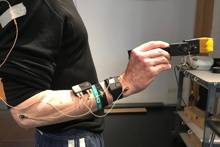 Photograph of a man holding a paintbrush with multiple sensors attached to his arm
