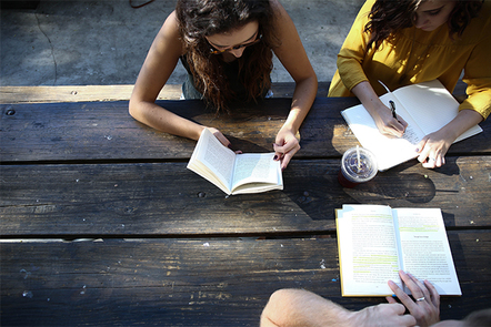 Arial view of three women studying on an outdoor wooden bend.