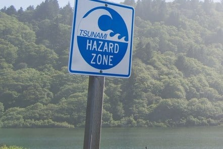 Tsunami hazard zone sign by a large lake with trees surrounding it