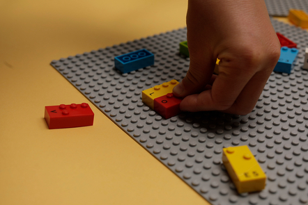 Image of a child's hands playing with LEGO Braille Bricks