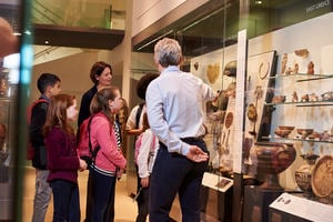 A group of children are shown a display in a museum