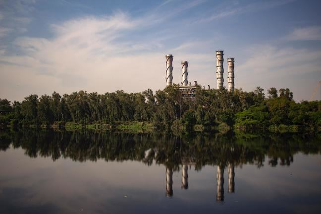 An industrial plant with four tall chimneys surrounded by trees close to a river bank reflection on the body of water.