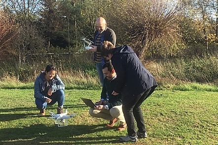 A group of four people are working togetether on a task - getting a drone to fly in a countryside setting