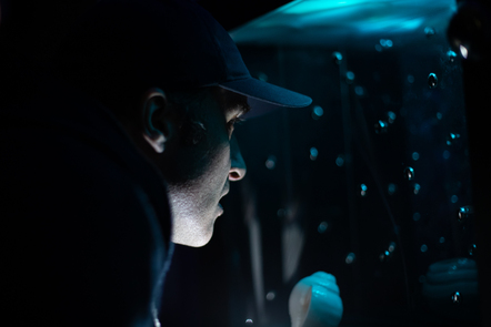 Decorative image, man looks into a screen with bubbles in it, it is dark but illuminated softly by blue light. Work by Karthika Sakthivel, image by Talie Eigeland 2020