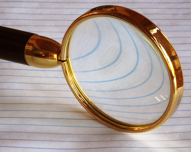 Magnifying glass over a page of blue parallel lines