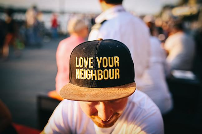 a man with his head down is wearing a hat that says 'love your neighbour' on it