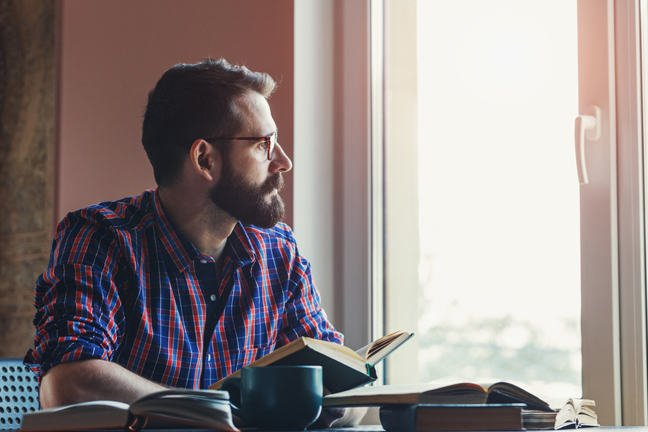 Man thinking while looking out of window and holding a book