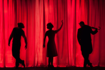three silhouettes of performers against red stage curtains
