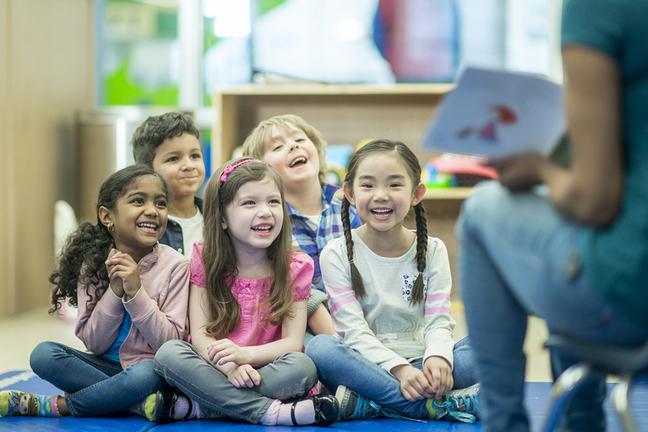 teacher reading to five diverse children