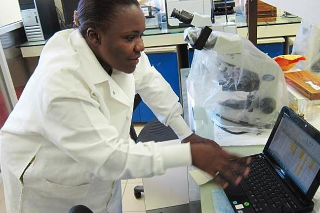 A Haitian woman in a white laboratory coat typing on a computer in a laboratory. There is also a large microscope on the work top, next to her computer. She is conducting blood sample evaluations.