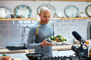 A man in a kitchen talking to camera with a plate of healthy food