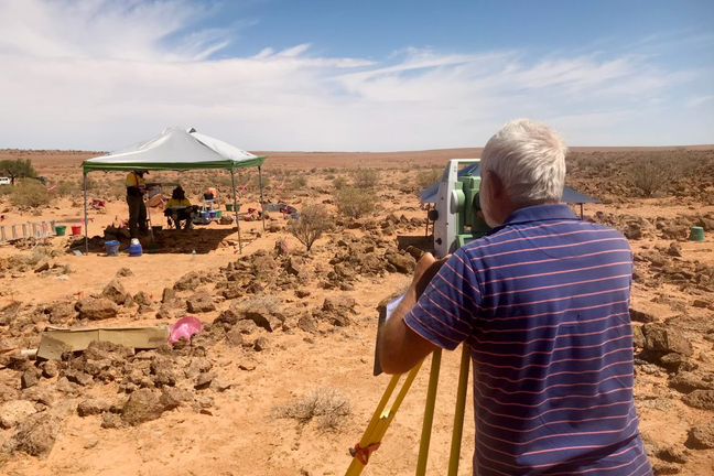 Ian Andrews surveying an archaeological while other researchers document the finds under a tent