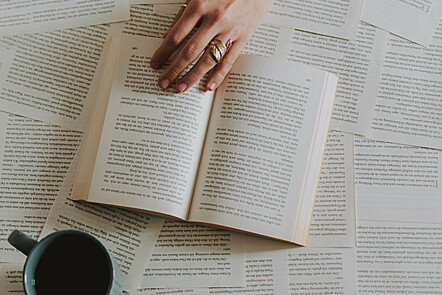 A book on top of a pile of pages from other books, vewed from above. A cup of coffee is placed on top of some of the papers from other books, and a hand is reaching to turn the page of the central book in the image.