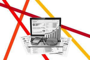 Laptop and printed documents displaying graphs and statistics