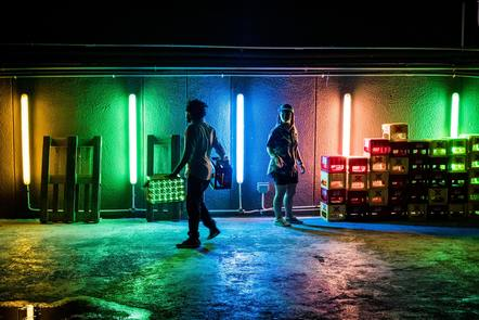 People working in a tunnel lit by different coloured neon lights