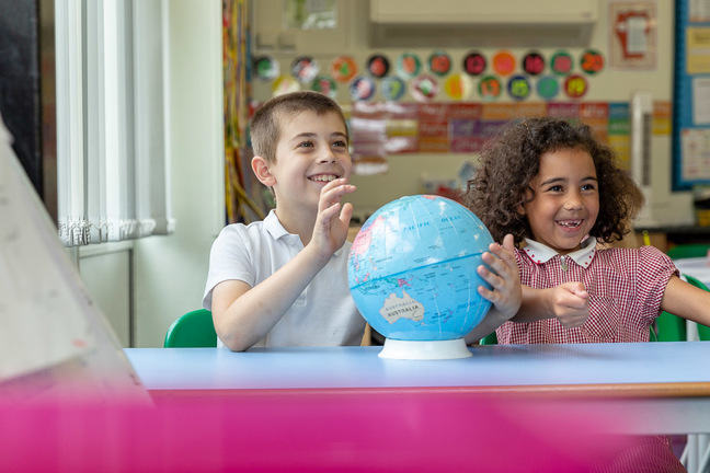 A photo of 2 children looking at a world globe.