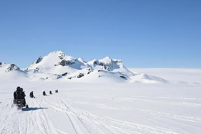 Image of a team of scientists snowmobiling across a snowy landscape