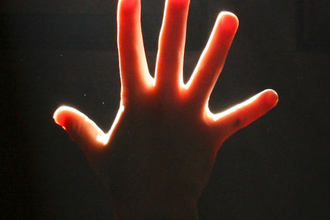 A hand illuminated against a dark background showing five fingers