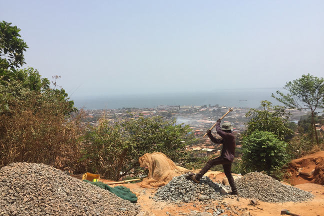 A man raising a hammer above his head to break the pile of rocks under his feet. There is a view of the city in the background.