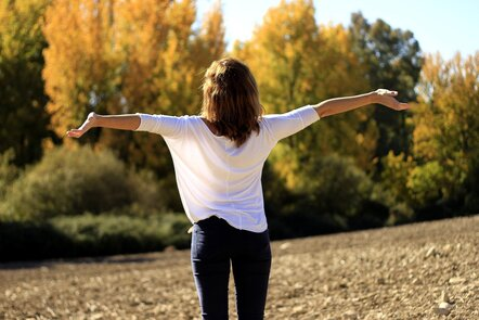 Image shows a person standing with their arms stretched out with trees in the background.