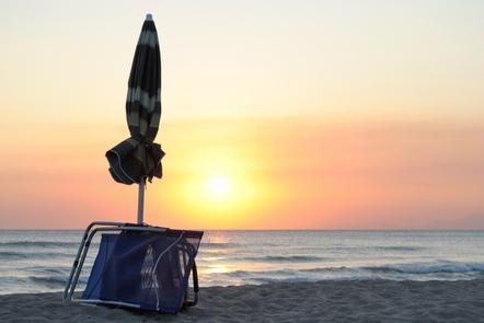 A folded parasol on a beach.