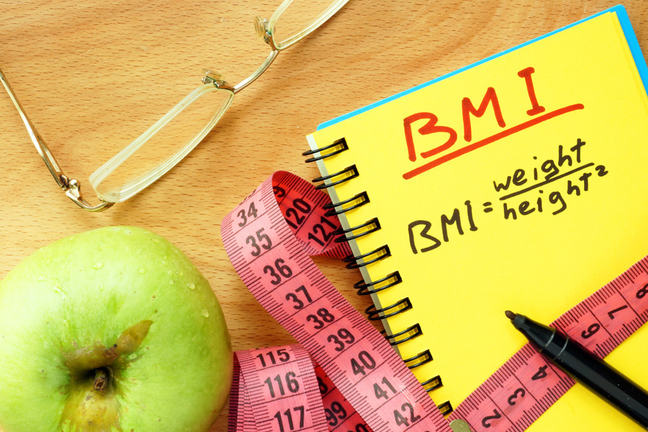 Photograph featuring an apple, spectacles, tape measure, pen and notepad. The formula for calculating a person's Body Mass Index (BMI) is written on the notepad.