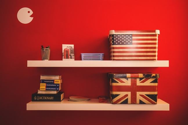 Two shelves with British and American dictionaries and flags, on a red background.