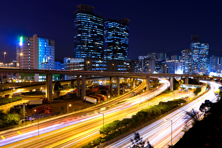 A night-time cityscape with lights and traffic.