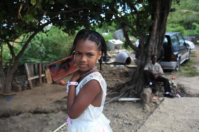 Young Haitiian girl with black braids and a white dress looks at the camera. Behind her is a man sitting on the ground leaning against a tree. There is a car parked behind the tree with rubble strewn around the yard.